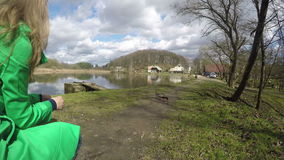 Ξανθή γυναίκα στα πράσινα πουλιά παπιών τροφών παλτών κοντά στη λίμνη 4K φιλμ μικρού μήκους