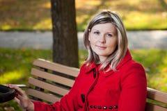 Ξανθή γυναίκα στην κόκκινο λαβή ή το καροτσάκι εκμετάλλευσης παλτών Στοκ φωτογραφία με δικαίωμα ελεύθερης χρήσης
