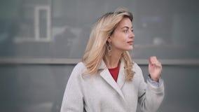 Ξανθή γυναίκα στο άσπρο παλτό που περιμένει κάποιο την πτώση στην οδό απόθεμα βίντεο
