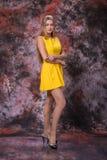 Ξανθή γυναίκα στο κίτρινο φόρεμα στο μαρμάρινο πολύχρωμο υπόβαθρο Πρότυπη δοκιμή στοκ φωτογραφίες