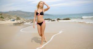 Ξανθή γυναίκα στο μαύρο μπικίνι που περπατά στην παραλία απόθεμα βίντεο