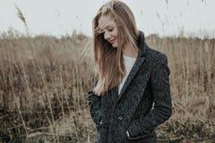 Ξανθή γυναίκα στο παλτό μαλλιού στο λιβάδι στοκ εικόνες
