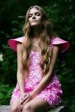 Ξανθή γυναίκα στο ρόδινο φόρεμα στο δάσος Στοκ φωτογραφία με δικαίωμα ελεύθερης χρήσης