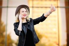 Ξανθή γυναίκα στο σακάκι μαύρων καπέλων και δέρματος που χρησιμοποιεί το κινητό τηλέφωνο Στοκ φωτογραφίες με δικαίωμα ελεύθερης χρήσης