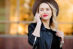 Ξανθή γυναίκα στο σακάκι μαύρων καπέλων και δέρματος που χρησιμοποιεί το κινητό τηλέφωνο Στοκ Εικόνες
