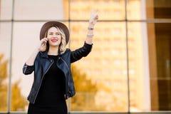 Ξανθή γυναίκα στο σακάκι μαύρων καπέλων και δέρματος που χρησιμοποιεί το κινητό τηλέφωνο Στοκ Εικόνα