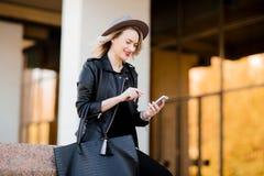 Ξανθή γυναίκα στο σακάκι μαύρων καπέλων και δέρματος και τσάντα που χρησιμοποιούν το κινητό τηλέφωνο Στοκ φωτογραφίες με δικαίωμα ελεύθερης χρήσης