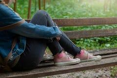 Ξανθή γυναίκα στο σακάκι τζιν και τα ρόδινα πάνινα παπούτσια καμβά που κάθεται σε έναν πάγκο πάρκων στοκ εικόνες με δικαίωμα ελεύθερης χρήσης
