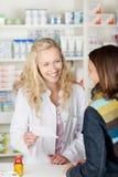Ξανθή γυναίκα φαρμακοποιών φαρμακείων στο φαρμακείο Στοκ Εικόνα