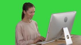 Ξανθή γυναίκα χρησιμοποιώντας τον υπολογιστή και έχοντας μια ιδέα που χαμογελά σε μια πράσινη οθόνη, κλειδί χρώματος απόθεμα βίντεο