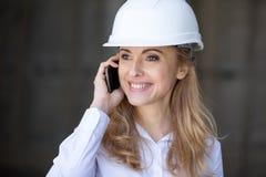 Ξανθή επιχειρηματίας στο σκληρό καπέλο που μιλά στο smartphone και που κοιτάζει μακριά Στοκ φωτογραφία με δικαίωμα ελεύθερης χρήσης