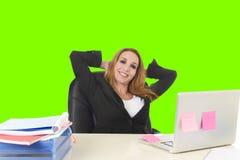 ξανθή επιχειρησιακή γυναίκα της δεκαετίας του '40 που εργάζεται χαλαρωμένο πράσινο κλειδί χρώματος γραφείων στο φορητός προσωπικό Στοκ φωτογραφία με δικαίωμα ελεύθερης χρήσης