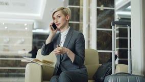 Ξανθή εύθυμη συνεδρίαση επιχειρηματιών στην πολυθρόνα στο λόμπι ξενοδοχείων που μιλά το κινητό τηλέφωνο και που η μάνδρα εκμετάλλ φιλμ μικρού μήκους