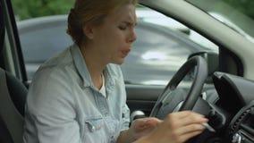 Ξανθή θηλυκή συνεδρίαση στο αυτοκίνητο και τον ισχυρό πονοκέφαλο συναισθήματος, που παίρνουν τα φάρμακα, ιατρική απόθεμα βίντεο