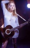 Ξανθή θηλυκή τοποθέτηση με την κιθάρα ενάντια στο Μαύρο Συνδυασμός λάμψης και αλόγονου χρησιμοποιούμενων Στοκ Εικόνες