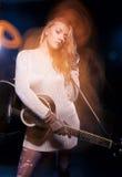 Ξανθή θηλυκή τοποθέτηση με την κιθάρα ενάντια στο Μαύρο Συνδυασμός λάμψης και αλόγονου χρησιμοποιούμενων Στοκ Εικόνα