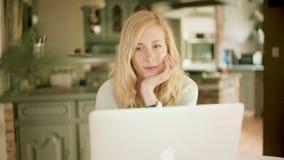 Ξανθή καυκάσια γυναίκα που εξετάζει στο σπίτι το χαμόγελο lap-top της απόθεμα βίντεο