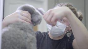 Ξανθή κομμένη τρίχα γυναικών groomer ενός poodle σκυλιού με το ψαλίδι Καλλωπισμός στην κλινική κτηνιάτρων φιλμ μικρού μήκους