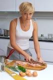 ξανθή κουζίνα κοριτσιών που καθιστά τα ζυμαρικά όμορφα στοκ εικόνα