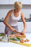 ξανθή κουζίνα κοριτσιών που καθιστά τα ζυμαρικά όμορφα στοκ φωτογραφία με δικαίωμα ελεύθερης χρήσης