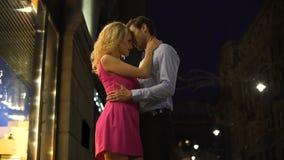 Ξανθή κυρία που αγκαλιάζει ήπια το αγαπημένο άτομό της, ρομαντική ημερομηνία στο κέντρο πόλεων νύχτας απόθεμα βίντεο