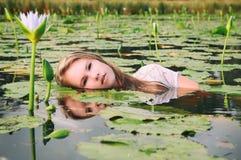 Ξανθή κυρία που επιπλέει μεταξύ των lillies Στοκ εικόνα με δικαίωμα ελεύθερης χρήσης