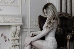 Ξανθή κυρία σε μια λεπτή συνεδρίαση φορεμάτων δαντελλών σε μια καρέκλα Στοκ φωτογραφία με δικαίωμα ελεύθερης χρήσης