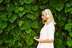 Ξανθή μουσική ακούσματος κοριτσιών τρίχας καυκάσια με τα ακουστικά Στοκ Εικόνες