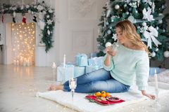 Ξανθή νέα γυναίκα με το φλυτζάνι της καυτής σοκολάτας μπροστά από τα φω'τα Χριστουγέννων και το χριστουγεννιάτικο δέντρο στοκ φωτογραφία με δικαίωμα ελεύθερης χρήσης