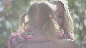 Ξανθή νέα γυναίκα που αγκαλιάζει και που φιλά την κόρη της στο φως ήλιων κοντά επάνω r Μητέρα και το παιδί της που στηρίζονται μέ φιλμ μικρού μήκους