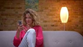 Ξανθή νοικοκυρά στο ρόδινο πουλόβερ που αγκαλιάζει το πόδι της και που κάνει τα όμορφα selfies στο smartphone στην άνετη εγχώρια  απόθεμα βίντεο