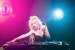ξανθή παίζοντας μουσική του DJ στη λέσχη στοκ φωτογραφία