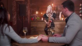 Ξανθή παίζοντας μουσική saxophonist για ένα νέο ζεύγος ερωτευμένο φιλμ μικρού μήκους