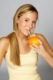 ξανθή πορτοκαλιά ρουφώντας γουλιά γουλιά γυναίκα χυμού Στοκ Εικόνες