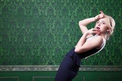 Ξανθή πρότυπη τοποθέτηση στο πράσινο εκλεκτής ποιότητας δωμάτιο Στοκ εικόνες με δικαίωμα ελεύθερης χρήσης