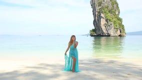 Ξανθή στάση κοριτσιών στην παραλία ενάντια στην ήρεμη διαφανή κυανή θάλασσα φιλμ μικρού μήκους