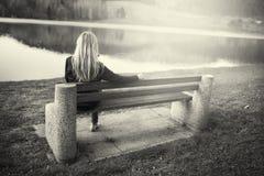 Ξανθή συνεδρίαση γυναικών στον πάγκο στη λίμνη Στοκ Εικόνες