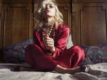 Ξανθή συνεδρίαση γυναικών στο κρεβάτι Στοκ εικόνα με δικαίωμα ελεύθερης χρήσης