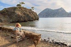 Ξανθή συνεδρίαση γυναικών στην ξύλινη καρέκλα κοντά στη Μεσόγειο Στοκ εικόνες με δικαίωμα ελεύθερης χρήσης
