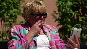 Ξανθή συνεδρίαση γυναικών στον πάγκο που καπνίζει και που μιλά στο skype φιλμ μικρού μήκους