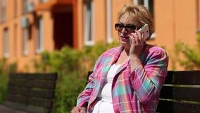 Ξανθή συνεδρίαση γυναικών στον πάγκο που καλεί και που μιλά στο τηλέφωνο απόθεμα βίντεο