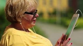 Ξανθή συνεδρίαση γυναικών στον πάγκο που καλεί και που μιλά στο skype φιλμ μικρού μήκους