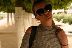 Ξανθή συνεδρίαση κοριτσιών στη σκιά Στοκ Φωτογραφίες
