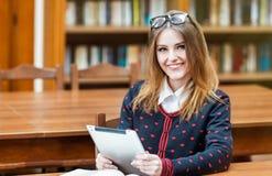 Ξανθή ταμπλέτα χρήσης κοριτσιών στη βιβλιοθήκη στοκ εικόνες