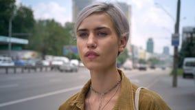 Ξανθή όμορφη γυναίκα με το σύντομο hairstyle που περιμένει το λεωφορείο ή το ταξί, που στέκεται στην οδό κοντά στο δρόμο φιλμ μικρού μήκους