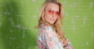 Ξανθή όμορφη γυναίκα στην τοποθέτηση γυαλιών ηλίου απόθεμα βίντεο