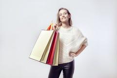 Ξανθή όμορφη καυκάσια γυναίκα με τις τσάντες εγγράφου αγορών στον ώμο Φθορά του θερμού πουλόβερ, χαμόγελο Στοκ φωτογραφία με δικαίωμα ελεύθερης χρήσης