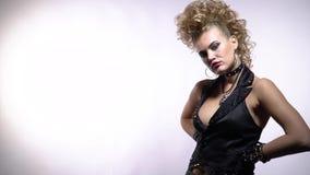 Ξανθή rocker γυναίκα που φορά την καρφωμένη φανέλλα και τα μαύρα γάντια, άσπρο υπόβαθρο απόθεμα βίντεο