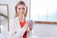 Ξανθομάλλης τοποθέτηση γυναικών με μια κούπα του καφέ Στοκ φωτογραφία με δικαίωμα ελεύθερης χρήσης