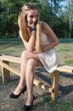 Ξανθομάλλης γυναίκα σε ένα πάρκο σε έναν πάγκο Στοκ εικόνα με δικαίωμα ελεύθερης χρήσης